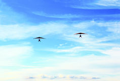 Two hang-glider. Two hang-glider flew through the sky with the help of people across the sky in the summer royalty free stock photo