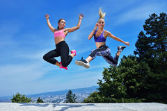 Two happiness young women jumping over blue sky Stock Photography