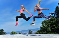 Two happiness young women jumping over blue sky Royalty Free Stock Images