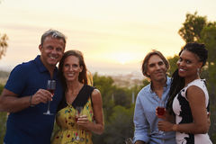 Two happy adult couples socialising outdoors look to camera stock image
