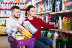 Two happy adult people in good spirits selecting detergents in t. Two happy adult people in good spirits selecting detergents оn the shelves in the store Stock Images