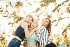 Happy meeting of two friends hugging in the street. Two happy affectionate young women hugging each other in a close embrace while laughing and smiling Royalty Free Stock Photos