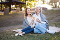 Two happy amused women sitting on the ground. Fantastic holiday. Pretty charming mother and daughter smiling and sitting on the ground while eating cakes royalty free stock photography