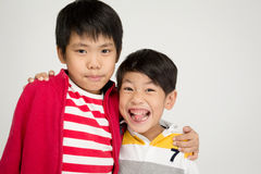 Two happy asian brothers hugging. On gray background and looking camera royalty free stock photography