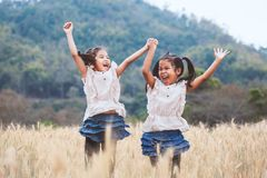 Two happy asian child girls having fun to play and jump in the barley field royalty free stock photos