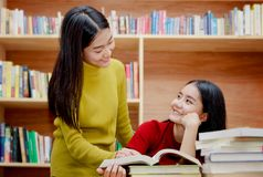 Happy Asian college student reading books in the library tog. Two happy Asian college student reading books in the library together Royalty Free Stock Images
