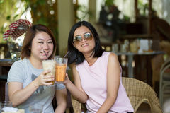 Two Happy asian Female in coffeeshop Cafe Royalty Free Stock Photos
