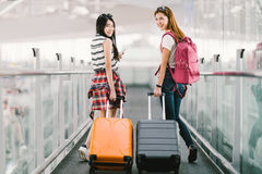 Two happy Asian girls traveling abroad together, carrying suitcase luggage in airport. Air travel or holiday vacation concept.  royalty free stock photos