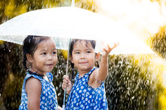 Two happy asian little girls with umbrella Royalty Free Stock Image