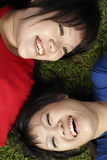 Two happy asian teen girls laughing. Two happy asian teen girls lying on grass, wearing red and blue laughing Royalty Free Stock Images