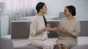 Two happy asian women drinking white wine, celebration of victory, partnership. Stock footage stock video