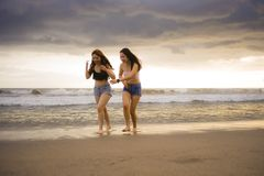 Two happy and attractive young Asian Chinese women girlfriends or sisters having fun walking on the beach laughing and talking bea royalty free stock photography