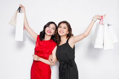 Two happy attractive young women with shopping bags on white bac Stock Photos