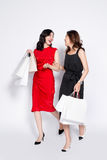 Two happy attractive young women with shopping bags on white bac Royalty Free Stock Images