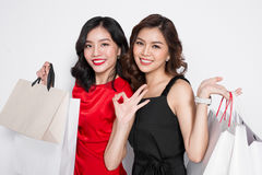 Two happy attractive young women with shopping bags on white bac Stock Images