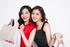Two happy attractive young women with shopping bags on white bac Royalty Free Stock Photos