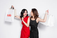 Two happy attractive young women with shopping bags on white bac Royalty Free Stock Image