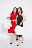 Two happy attractive young women with shopping bags on white bac Royalty Free Stock Photo