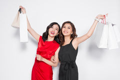 Two happy attractive young women with shopping bags on white bac Stock Photo