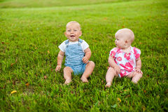 Free Two Happy Baby Boy And A Girl Age 9 Months Old, Sitting On The Grass And Interact, Talk, Look At Each Other. Royalty Free Stock Photo - 82184195