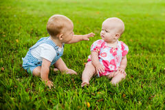 Free Two Happy Baby Boy And A Girl Age 9 Months Old, Sitting On The Grass And Interact, Talk, Look At Each Other. Stock Photo - 82184260