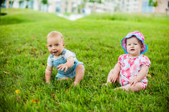 Two happy baby boy and a girl age 9 months old, sitting on the grass and interact, talk, look at each other. Royalty Free Stock Photography