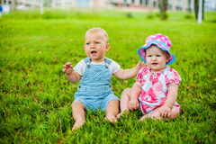 Two happy baby boy and a girl age 9 months old, sitting on the grass and interact, talk, look at each other. Royalty Free Stock Image