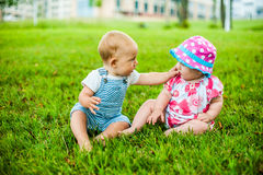 Two happy baby boy and a girl age 9 months old, sitting on the grass and interact, talk, look at each other. Stock Images