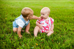 Two happy baby boy and a girl age 9 months old, sitting on the grass and interact, talk, look at each other. Kids are resting on a hot summer day on the grass Stock Image