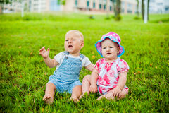 Two happy baby boy and a girl age 9 months old, sitting on the grass and interact, talk, look at each other. Stock Photo