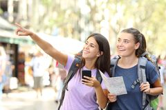 Two backpackers sightseeing pointing at landmark. Two happy backpackers sightseeing in a big city street pointing at landmarks stock photography