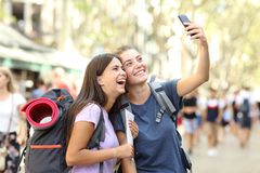 Two happy backpackers taking selfies in the street on vacation royalty free stock photos
