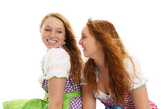 Two happy bavarian dressed women looking at each o. Ther on white background Stock Image