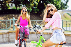 Two happy beautiful girls on a bicycles Royalty Free Stock Image