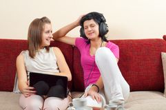 Two happy beautiful girls listening to music Stock Photo