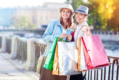 Two happy beautiful girls with shopping bags in the city Royalty Free Stock Image