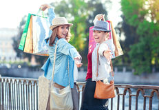 Two happy beautiful girls with shopping bags in the city Stock Photos