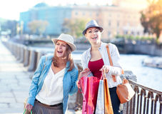 Two happy beautiful girls with shopping bags in the city Stock Image