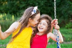 Two happy beautiful girls sitting on seesaw and smiling at warm. Sunny day Royalty Free Stock Images