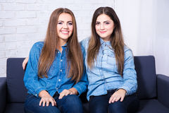 Two happy beautiful girls sitting on sofa in living room Stock Photos
