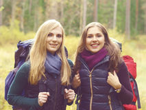 Two happy and beautiful girls walking in forest and swamps. Camp Stock Photography