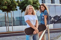 Two happy beautiful hipster girls standing with skateboard on a background of the skyscraper. royalty free stock image