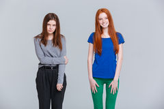 Two happy beautiful and sad pretty young women. Two happy and sad young women standing over white background stock photography