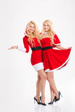 Two Happy Beautiful Sisters Twins Hugging  In Santa Claus Costumes