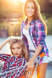 Two happy beautiful teen girls driving shopping cart outdoors Royalty Free Stock Photo