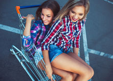 Two happy beautiful teen girls driving shopping cart outdoors. Lifestyle concept Royalty Free Stock Photos