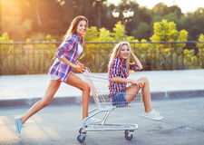 Two happy beautiful teen girls driving shopping cart outdoors. Lifestyle concept Stock Images