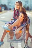 Two happy beautiful teen girls driving shopping cart outdoors stock photography
