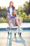 Two happy beautiful teen girls driving shopping cart outdoors. Lifestyle concept Royalty Free Stock Photo