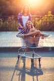 Two happy beautiful teen girls driving shopping cart outdoors Royalty Free Stock Image